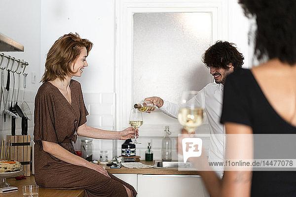 Freunde amüsieren sich auf einer Party  trinken Wein in der Küche
