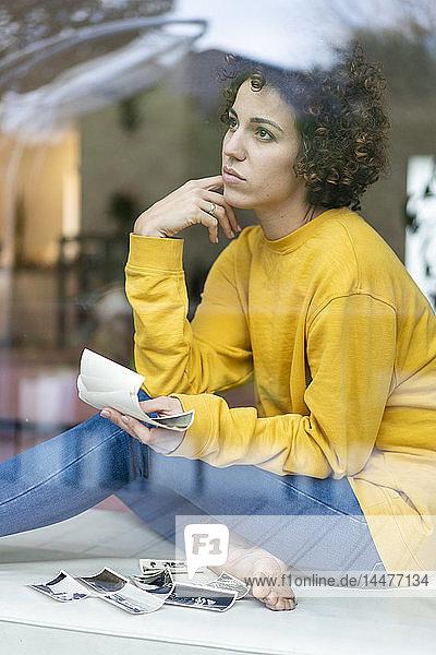 Seriöse Frau sitzt zu Hause hinter dem Fenster und hält Fotos