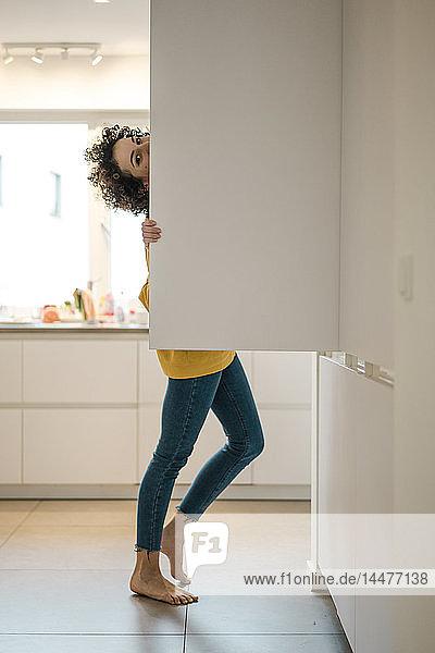Porträt einer Frau am Kühlschrank in der heimischen Küche