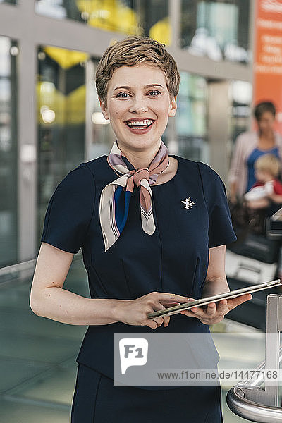 Portrait of happy airline employee holding tablet at the airport