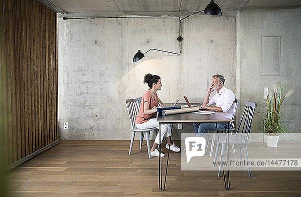 Lächelnder Geschäftsmann und Geschäftsfrau bei der Arbeit am Tisch in einem Loft