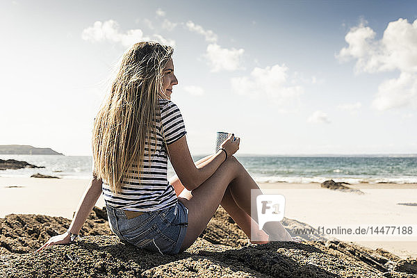 Young woman sitting in a rock at the beach  relaxing with a cup of tea