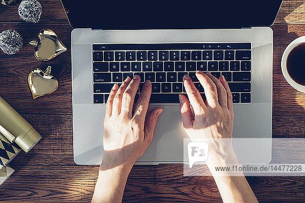 Frauenhände beim Tippen am Laptop  Draufsicht
