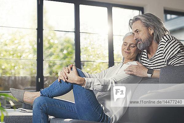 Glückliches älteres Ehepaar sitzt zu Hause