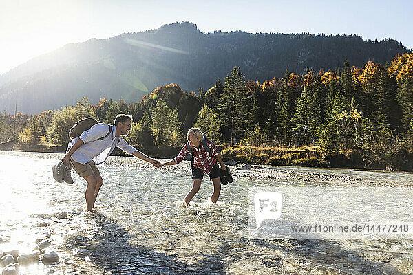 Österreich,  Alpen,  Ehepaar auf einer Wanderung watend in einem Bach