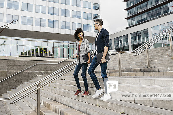 Two colleagues walking and talking on stairs outside office building in the city