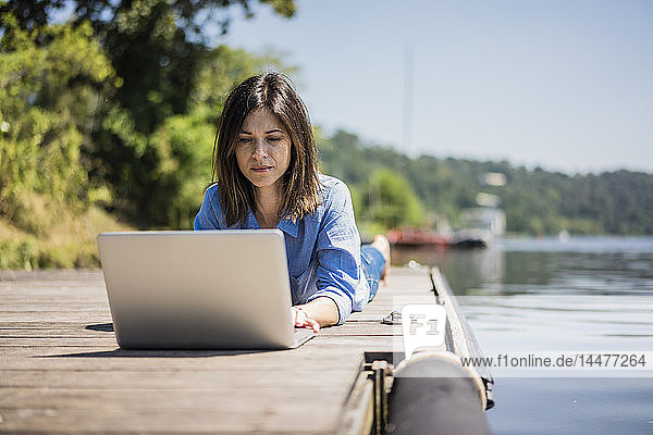 Mature woman working at a lake  using laptop on a jetty