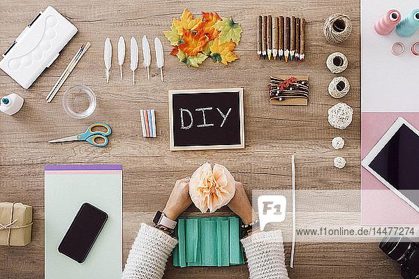 Draufsicht einer jungen Frau  die in ihrem Atelier mit Papierblumen bastelt