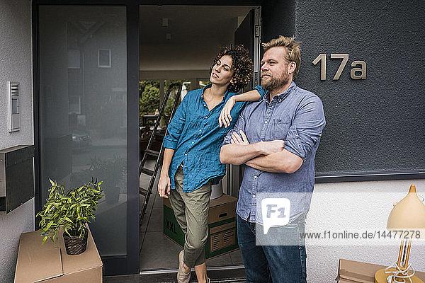 Paar steht mit Pappkartons am Hauseingang