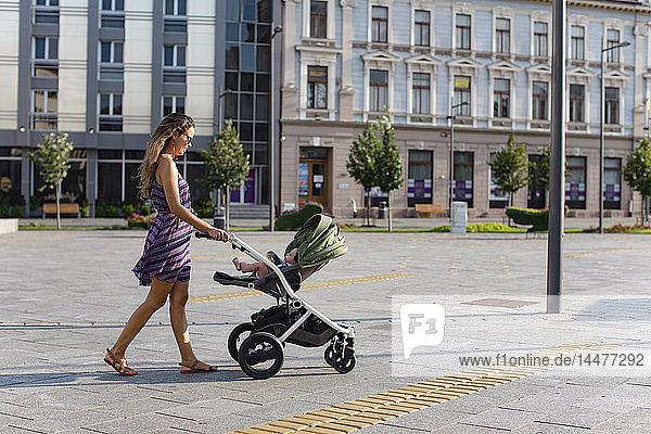 Mutter stößt ihr Kind im Kinderwagen in der Stadt
