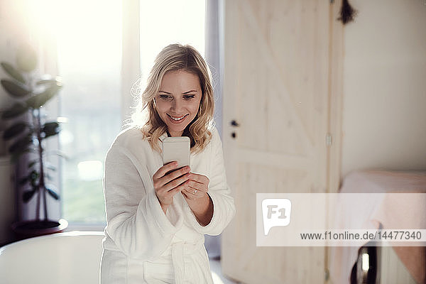 Smiling woman wearing bathrobe in bathroom at home holding cell phone