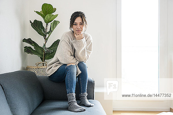 Woman sitting on her couch  looking at camera
