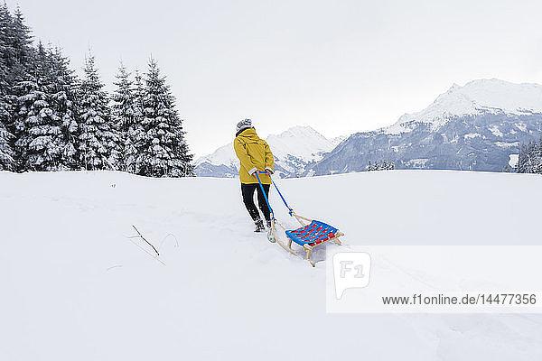 Österreich  Tirol  Thurn  Rückenansicht einer Schlitten ziehenden Frau in schneebedeckter Landschaft