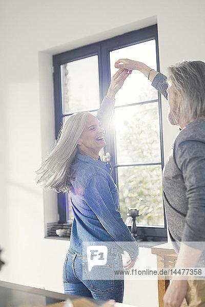 Jugendliches Seniorenpaar tanzt in der Küche