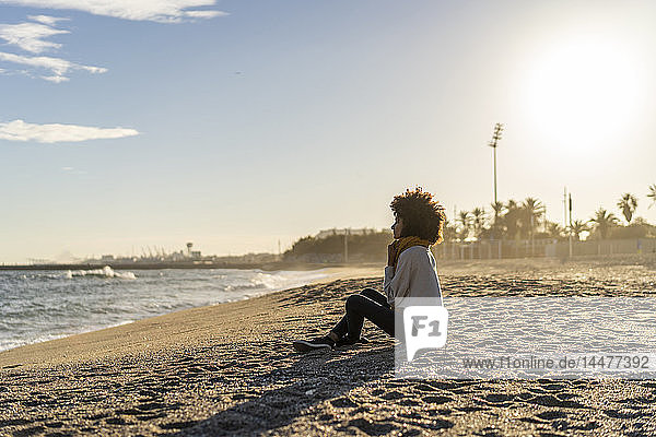 Woman sitting on the beach at sunset