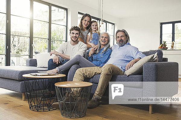 Großfamilie sitzt auf dem Sofa und lächelt glücklich