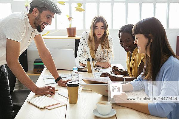 Lächelnde Kollegen arbeiten zusammen am Schreibtisch im Büro