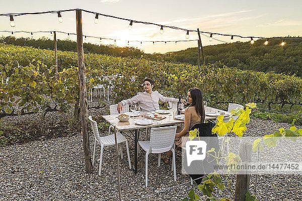 Italien  Toskana  Siena  junges Paar beim Abendessen in einem Weinberg