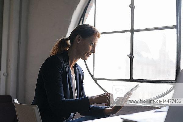 Geschäftsfrau mit Tablett am Fenster im Büro