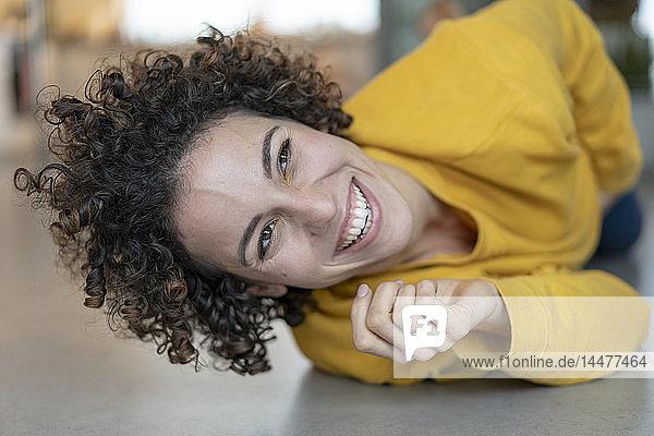 Porträt einer glücklichen Frau  die zu Hause auf dem Boden liegt