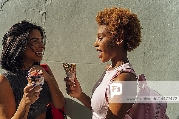 Two happy female friends with ice cream cones talking at a wall