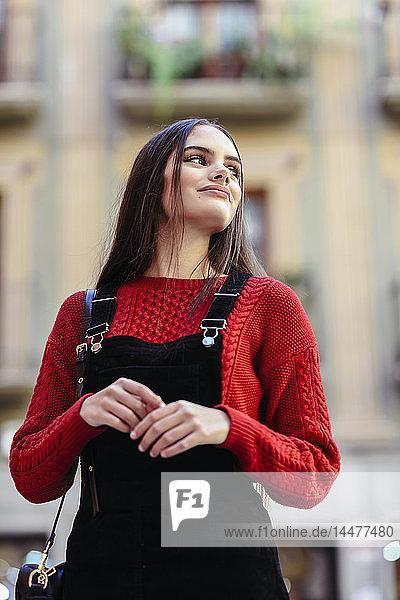 Porträt einer modischen jungen Frau in rotem Strickpullover und schwarzem Trägerkleid