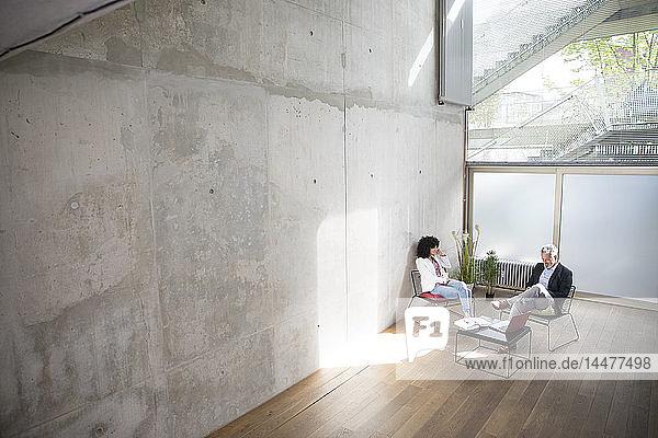 Geschäftsmann und Geschäftsfrau sitzen in einem Loft an einer Betonmauer