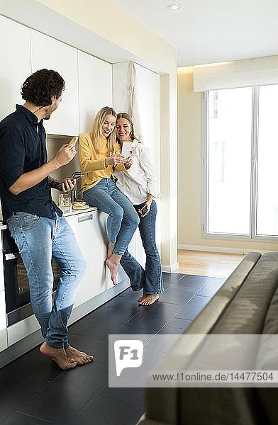 Freunde haben Spaß daran  in der Küche zu stehen und Smartphones zu benutzen
