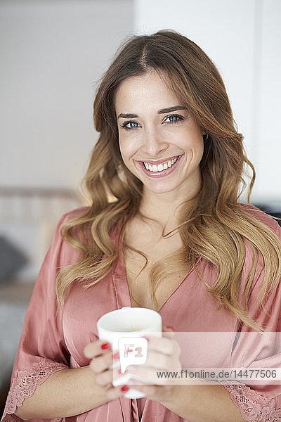 Porträt einer lächelnden jungen Frau im Bademantel mit einer Tasse Kaffee in der Hand