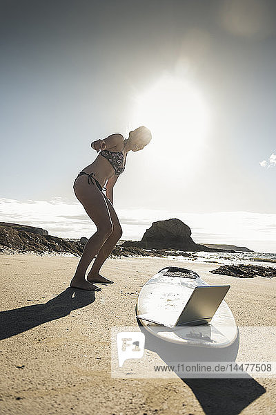 Young woman standing by surfboard  using laptop