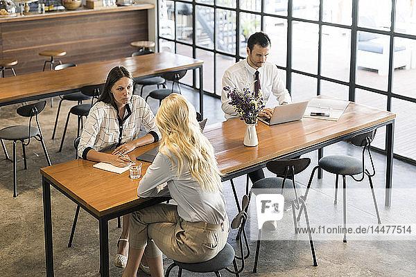 Kollegen diskutieren und arbeiten am Laptop auf einem Holztisch im Cafe