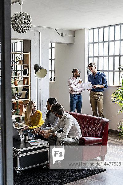 Geschäftsteam benutzt Laptop und bespricht Dokumente im Loft-Büro