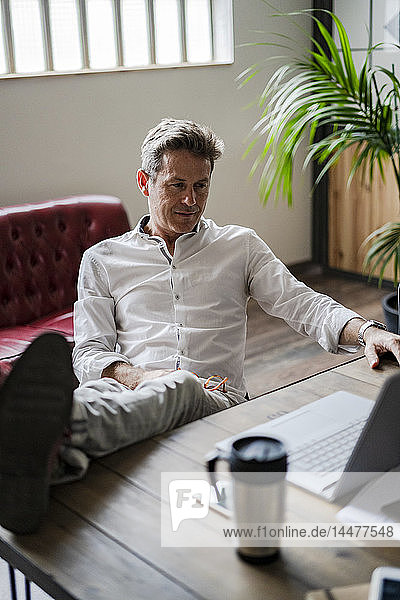 Businessman sitting with feet on desk looking at laptop