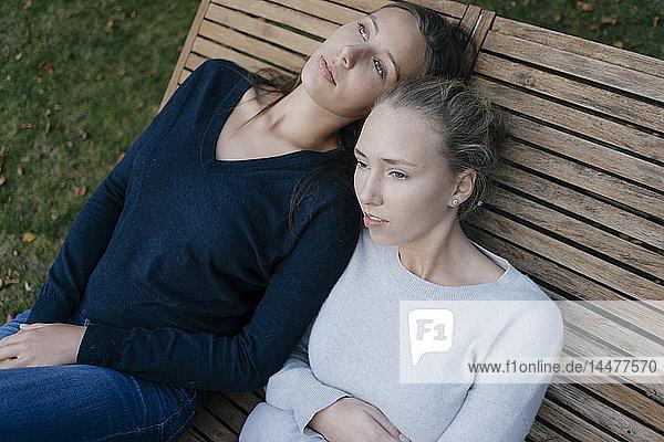 Zwei liebevolle  nachdenkliche Teenager-Mädchen ruhen sich auf einer Sonnenliege aus