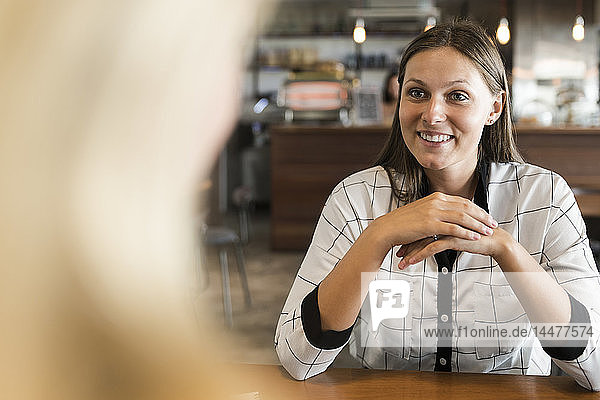 Smiling young businesswoman in cafe talking to colleague
