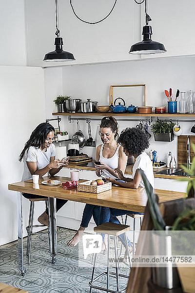 Drei glückliche Frauen sitzen zu Hause am Küchentisch und benutzen Mobiltelefone