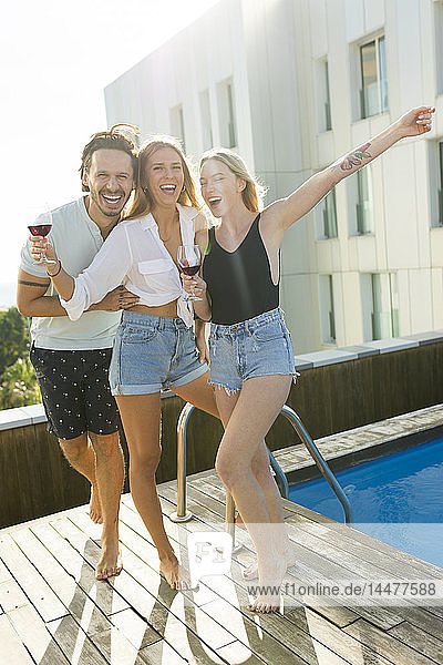 Freunde  die sich am Dachpool amüsieren und Rotwein trinken