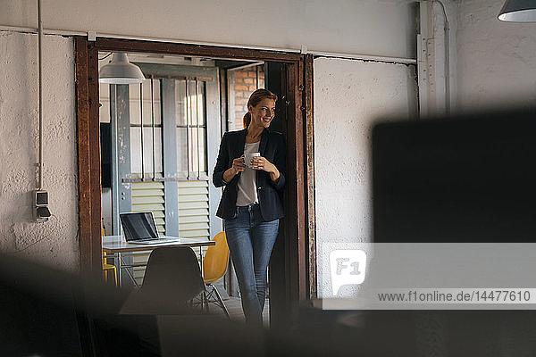 Lächelnde Geschäftsfrau bei einer Kaffeepause im Büro