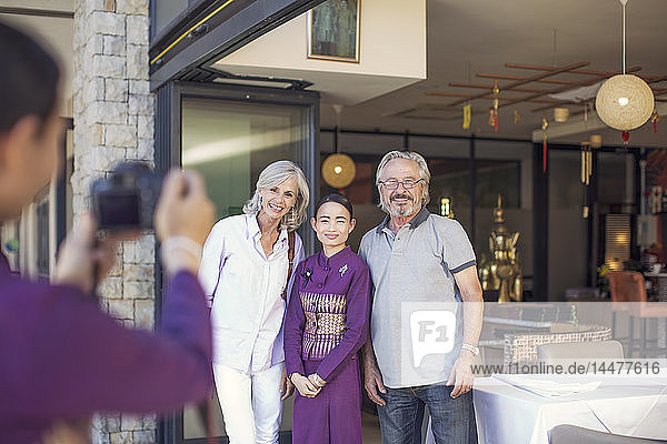 Älteres Ehepaar beim Fotografieren mit asiatischer Kellnerin vor einem Restaurant