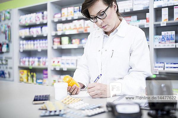 Apotheker mit Medikament am Schalter in der Apotheke