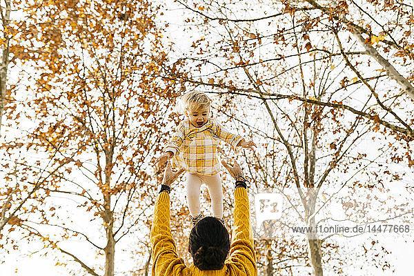 Vater wirft seine Tochter in die Luft  im Herbst in einem Park