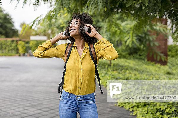 Glückliche Frau  die im Freien mit Kopfhörern Musik hört