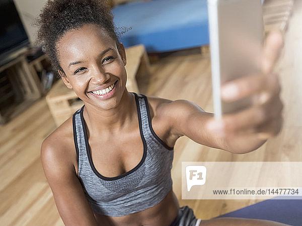 Lächelnde junge Frau in Sportkleidung nimmt ein Selfie