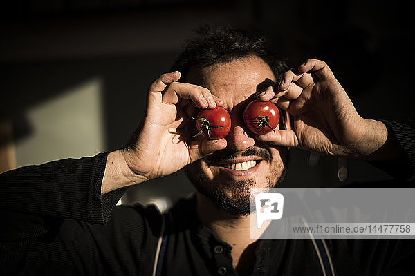 Mann bedeckt seine Augen mit Tomaten