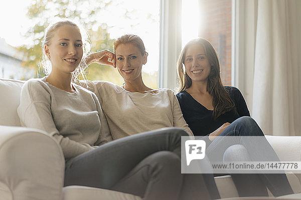 Porträt einer lächelnden Mutter mit zwei Mädchen im Teenager-Alter,  die zu Hause auf der Couch sitzen