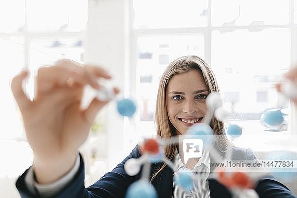 Weibliche Wissenschaftlerin untersucht Molekülmodell