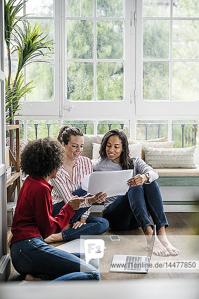Three women with laptop and documents sitting on the floor at home