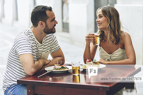 Smiling couple eating and drinking beer in a restaurant on the street