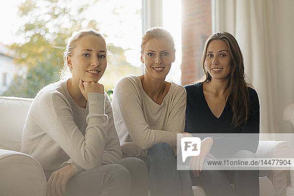Porträt einer lächelnden Mutter mit zwei Mädchen im Teenager-Alter  die zu Hause auf der Couch sitzen