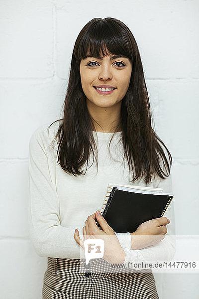 Porträt einer lächelnden jungen Frau mit Notizbuch an der Ziegelmauer